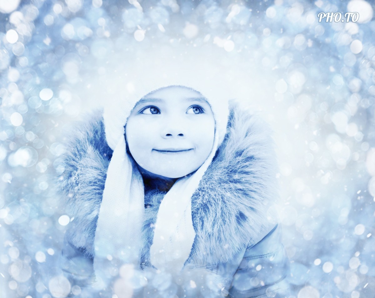 Winter portrait of a cute little girl is edited with blue bokeh effect