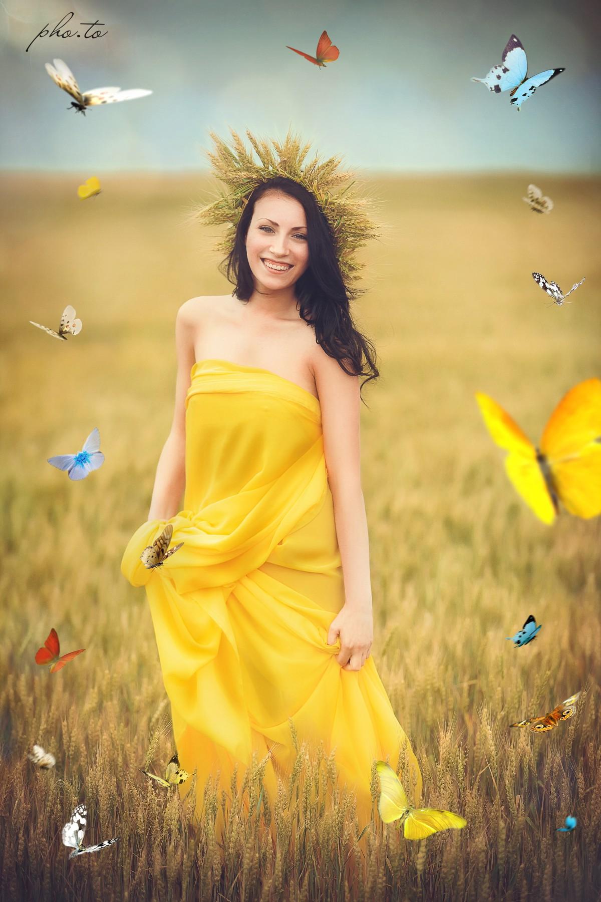 Summer shot of a beautiful girl adorned with butterflies overlay
