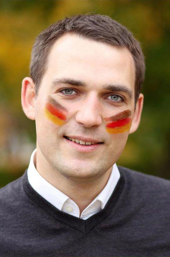 Sympatischer Mann mit Deutschland Schminke im Gesicht.