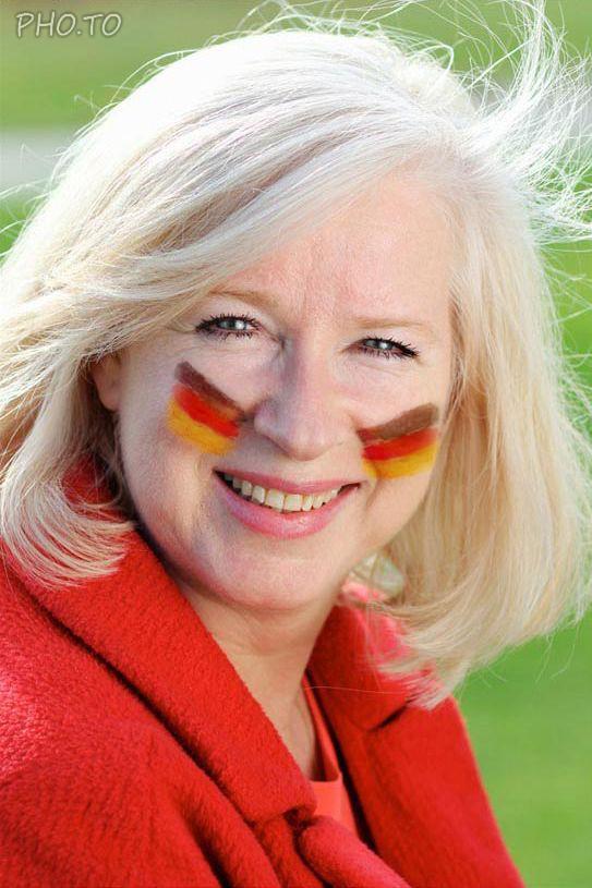 Lachende Frau mit Deutschland Schminke im Gesicht.