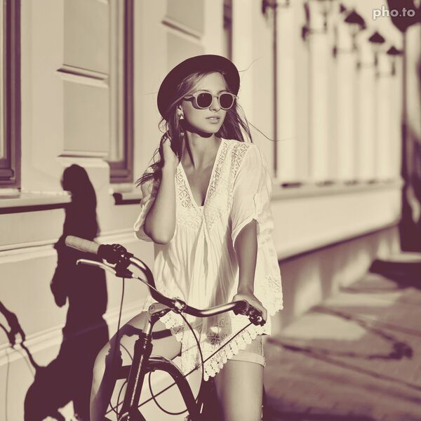 Photo of a beautiful girl on a bicycle in vintage style.